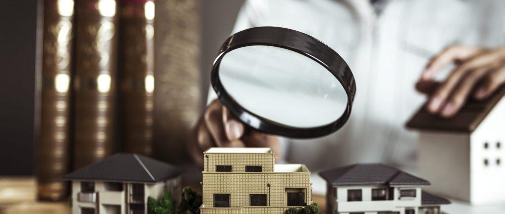住宅模型をルーペで覗く作業服の男性